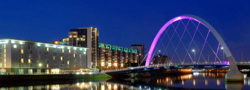 Photograph of Clyde Arc bridge lit up at night.